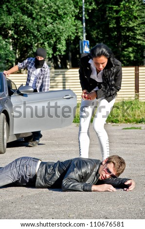 Male thief stealing a car while his accomplice distracts female driver - stock photo