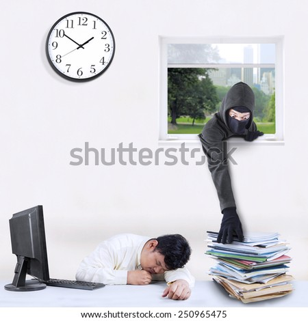 Male thief with a mask take document through a window while the employee is sleeping - stock photo