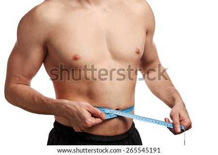 Male torso with measure tape on waistline over white background - stock photo