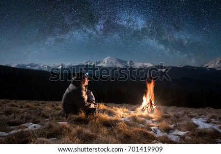 Male tourist have a rest in the mountains at night. Man with a headlamp sitting near campfire under beautiful night sky full of stars and milky way, and enjoying night scene