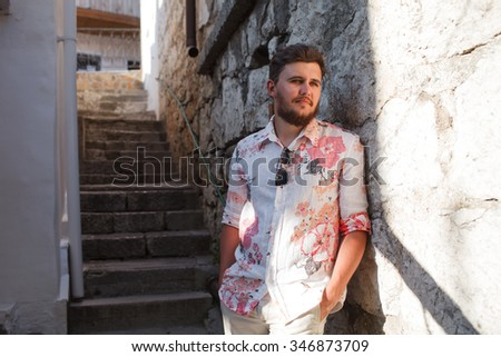 Male tourist in small summer town wearing bright shirt, hat and sunglasses getting rest and relax