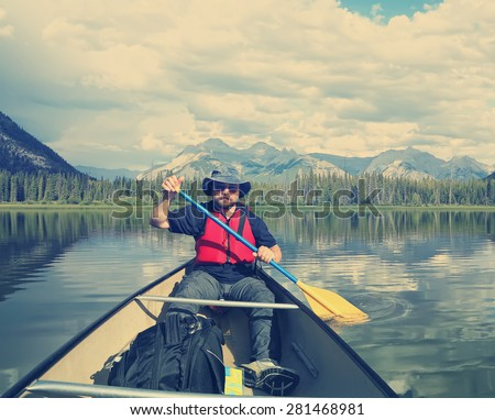Male tourist paddling a canoe on the mountain  lake. Vermillion Lakes. Banff National Park, Alberta, Canada). Image done in vintage retro instagram style  - stock photo