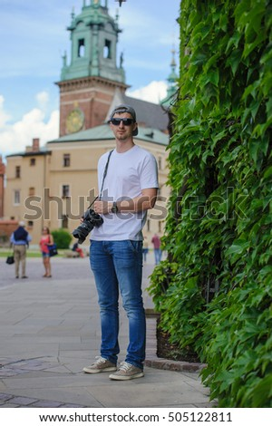 Male tourist takes picture in historic city in Cracow, Poland.