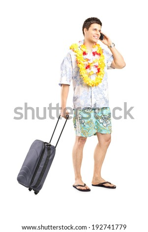 Male tourist taking on the phone and carrying his luggage isolated on white background - stock photo