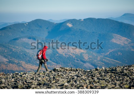Male tourist walking on the rocky mountain ridge with beautiful mountains on background. Man is wearing red jacket and has trekking sticks and backpack on. Sunny fall day.