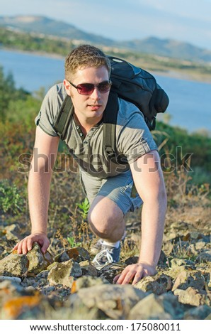 Male tourist with backpack climbs a mountain. - stock photo