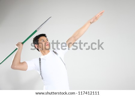 Male track athlete preparing to throw javelin - stock photo