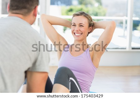 Male trainer assisting fit woman in doing sits up in exercise room - stock photo