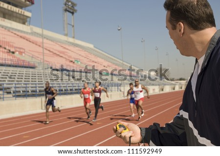 Male trainer measuring time while athletes racing - stock photo