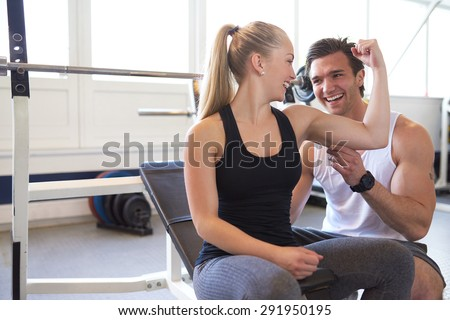 Male Trainer Testing Size of Blond Woman Bicep Muscle, Playful Couple Checking Muscles and Smiling at Each Other in Brightly Lit Gym - stock photo