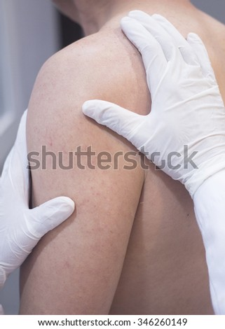 Male Traumatologist orthopedics surgeon doctor examining middle aged man patient to determine injury, pain, mobility and to diagnose medical treatment in shoulder, arm, elbow and wrist.  - stock photo