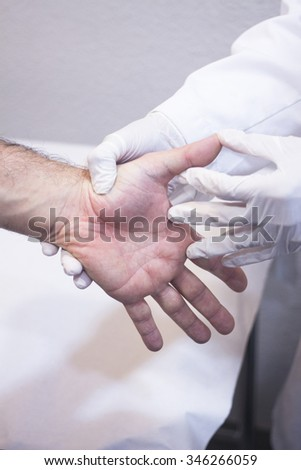 Male Traumatologist orthopedics surgeon doctor examining middle aged man patient to determine injury, pain, mobility and to diagnose medical treatment in hand fingers and wrist. - stock photo