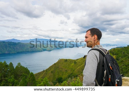 Male traveler looking at Toba lake in North Sumatra, Indonesia. Young man living active life