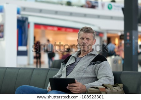 male traveler with the laptop uses a Wi-Fi with expectation of the flight - stock photo