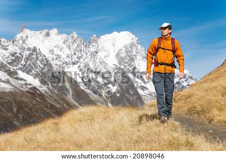 Male trekker walks along a mountain path, in background the Grand Jourasses peaks, fall season; Val Veny, Mont Blanc massif, Courmayeur, Italy - stock photo