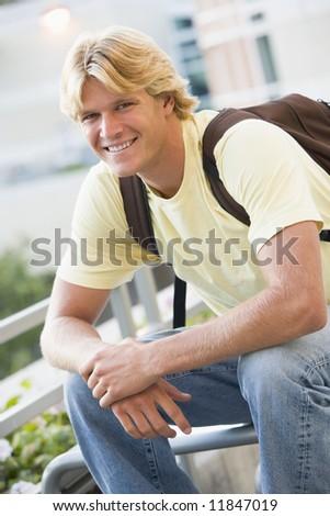 Male university outside wearing rucksack - stock photo