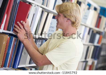 Male university student selecting book from library shelf - stock photo