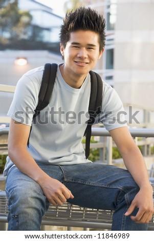 Male university student sitting outside wearing rucksack - stock photo