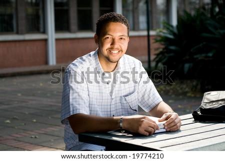 male university student study books outdoor - stock photo