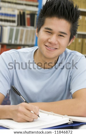 Male university student writing report in library - stock photo