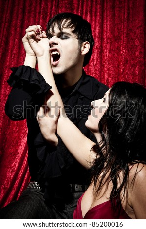 Male vampire is going to bite into a womans wrist. His mouth is open so you can see his fangs. - stock photo