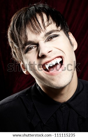 Male vampire laughing dangerously and showing his fangs - stock photo