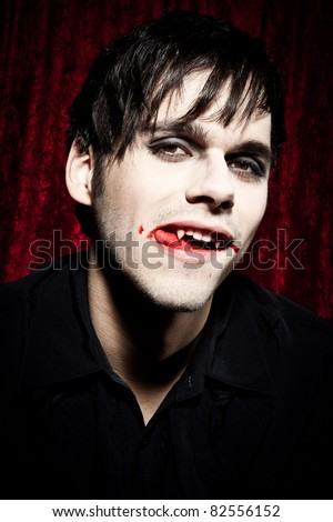 Male vampire licking his bloody lips II - stock photo