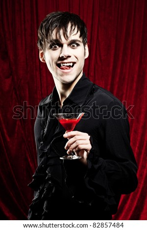 Male vampire wants to drink a glass of blood - stock photo