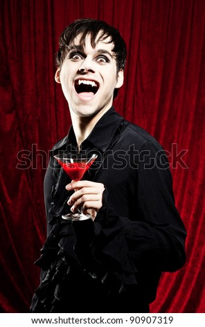 Male vampire with a glass of red blood in his hands, looking dangerous - stock photo