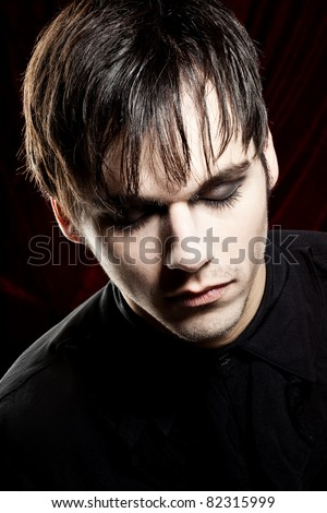 Male Vampire with mouth closed is looking down - stock photo