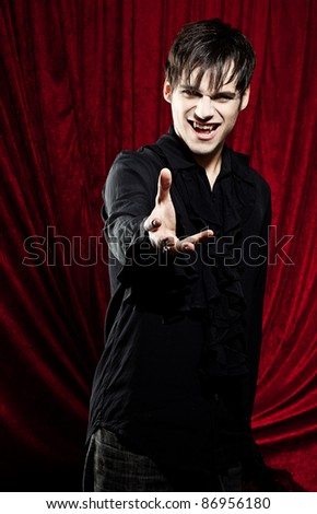 Male vampire with stretched out hand. - stock photo