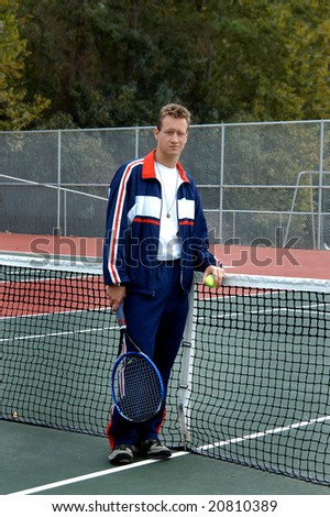 Male varsity tennis player wears his navy and red warm-up and stands besides net with racket and ball. - stock photo