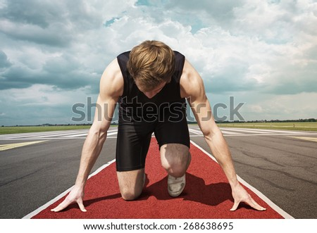 Male version of airport runway starter. Runner in start position kneels with lowered head on a red tartan surface, ready to take of. - stock photo