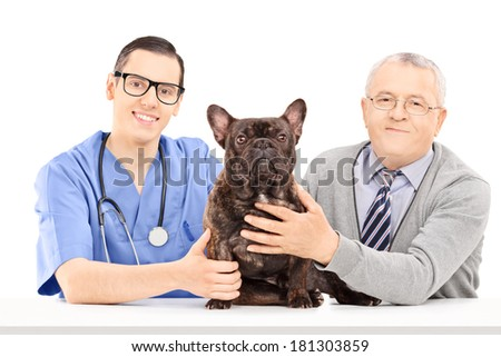 Male veterinarian, a dog and an elderly gentleman posing seated at a table isolated on white background - stock photo