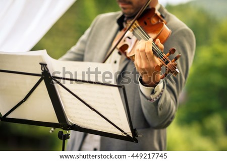 Male violinist playing his instrument and reading a music sheet during an outdoor summer wedding ceremony (shallow DOF; color toned image) - stock photo