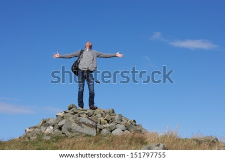 Male Walker Standing On Pile Of Rocks - stock photo