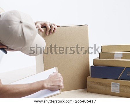 male warehouse worker checking and recording packages received. - stock photo