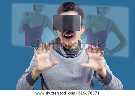 Male watching 3D virtual reality sexy movie  The man is doing lustful gestures and the female model face is obscured. - stock photo