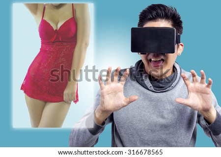 Male watching 3D virtual reality sexy movie with headset.  The man is doing lustful gestures and the female model face if obscured. - stock photo