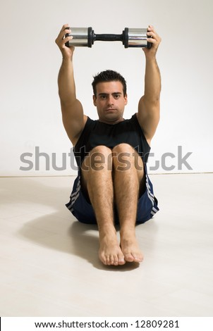 Male weightlifter / athlete doing a sit-up with a dumbbell weight. - stock photo