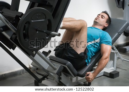 Male weightlifter doing leg presses. - stock photo