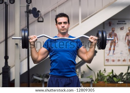 Male weightlifter, looking straight into camera, holding barbell weights. - stock photo
