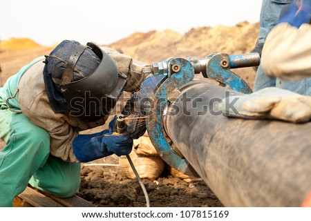 Male welder worker wearing protective clothing fixing and joining industrial construction oil and gas or water plumbing pipeline using an external pipe clamp outside on site - stock photo
