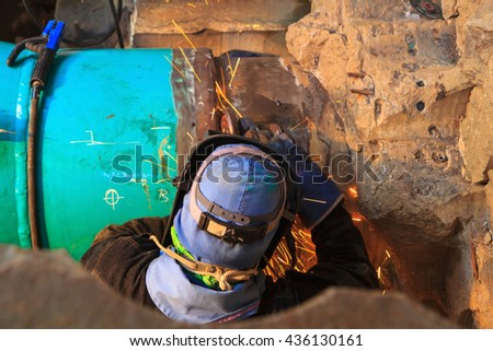 Male welder worker wearing protective clothing fixing Repair Pipeline welding and grinding industrial construction oil and gas or  pipeline inside confined spaces. - stock photo
