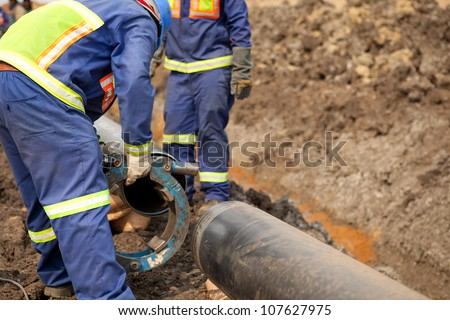 Male welder workers wearing protective high visibility clothing fixing and joining industrial construction oil and gas or water plumbing pipeline using an external pipe clamp outside on site