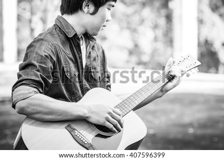Male with acoustic guitar outdoor, Black and white photo - stock photo