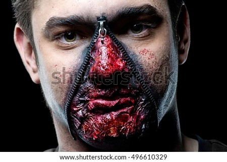 Male with horror make up in the studio on a black background. Halloween make up.