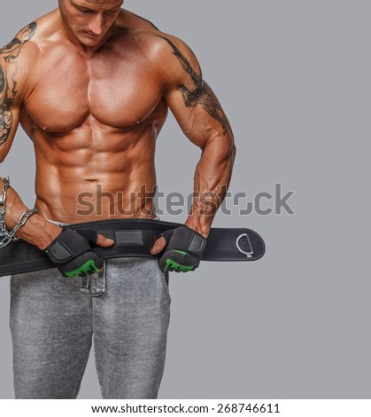 Male with muscular torso holding power weist. Isolated on grey - stock photo
