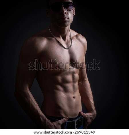 Male with naked torso on a black background - stock photo