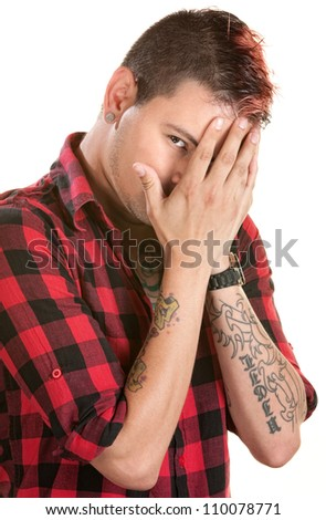 Male with spiky hair hiding behind his hands - stock photo